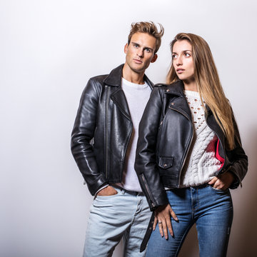 Young beautiful couple in black leather jackets pose in studio.