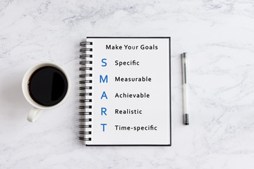 SMART goals writing on notebook. Notebook on desk with coffee cup and a pen.