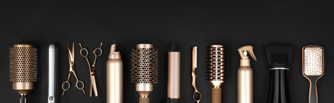 Collection of professional hair dresser tools arranged on dark background