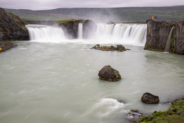 Iceland landscape scenic view of Godafoss waterfall against cloudy sky. It is one of the famous tourist attractions. It is a spectacular Icelandic waterfall on the North of island
