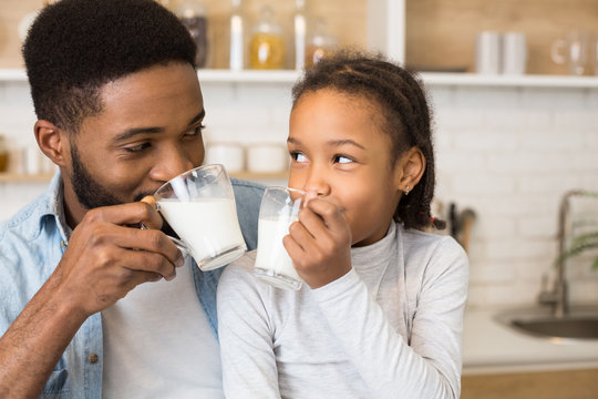 Black girl and her father drinking fresh milk