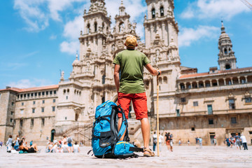 Young backpacker man pilgrim standing on the Obradeiro square (plaza) - the main square in Santiago de Compostela as a end of his Camino de Santiago pilgrimage. Fotomurales