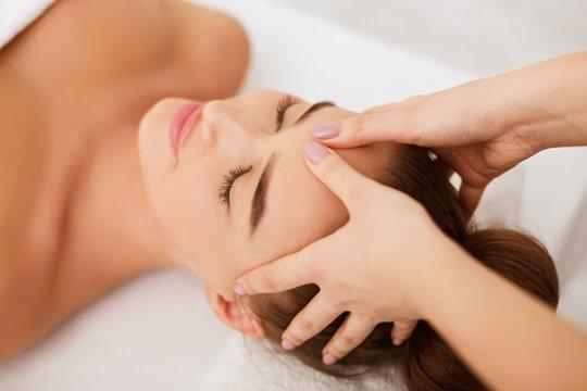 Woman enjoying head massage at spa center