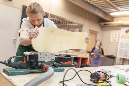 Scandinavian hipster carpenter makes a skateboard and polishes the board with a professional grinding machine. Concept of man at work on wood