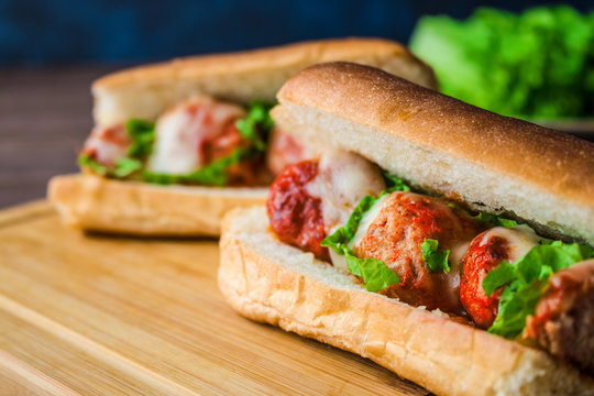 meatball sandwiches with mozzarella and lettuce  on cutting board