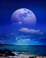 Wall Murals Dark blue Beautiful sky with super moon behind partial cloudy over seascape. Serenity nature background.