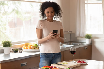 African woman standing in kitchen distracted from cooking using cellphone
