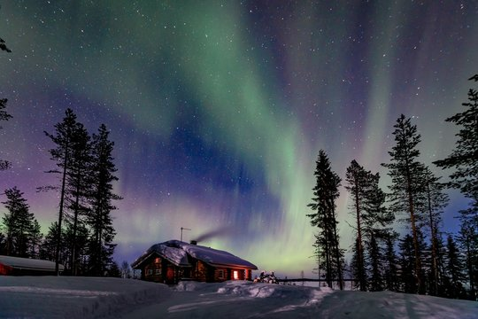 Polar arctic Northern lights Aurora Borealis activity over wooden house in winter Finland, Lapland