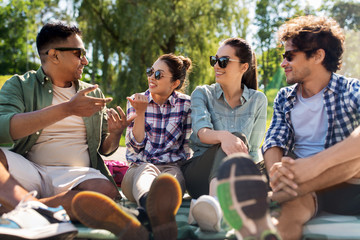 leisure, picnic and people concept - friends hanging out and talking outdoors in summer park Wall mural