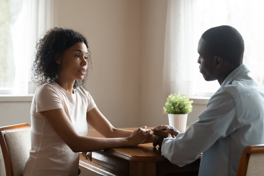African couple sitting at table having heart-to-heart talk
