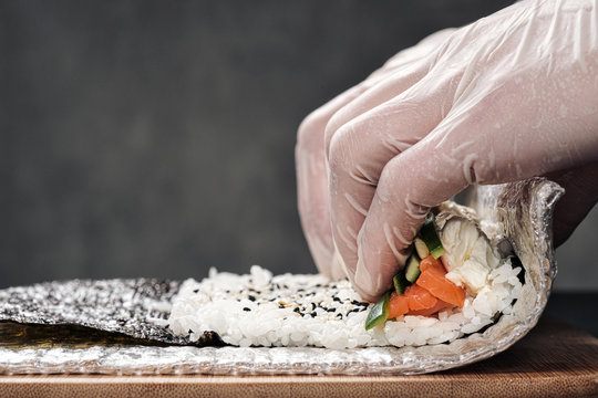 Cook's hands close-up. A male chef makes sushi and rolls from rice, red fish and avocado. White gloves.