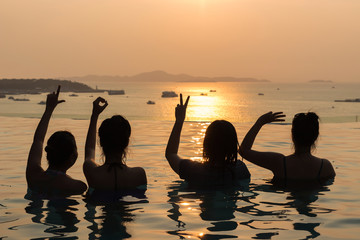 Silhouette of ladies show LOVE hands in a pool by the ocean