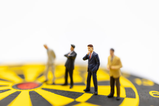 Business, Planning, Succession and Management Concept. Close up of group of businessman miniature figure standing and thinking on yellow and black dart board on white background.