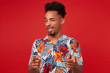 Young African American man wears in Hawaiian shirt, looks at the camera and winks, shows fingers to the camera and says