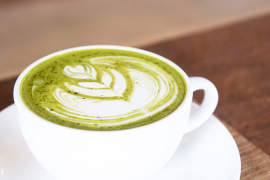 Coffee cup with Green Matcha latte art foam on wood table in coffee shop with copy space.Coffee is one of the most popular beverages.Improve Energy Levels and Burn Fat