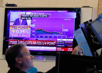 A trader looks on as a screen displays the U.S. Federal Reserve interest rates announcement on the floor of the New York Stock Exchange (NYSE) in New York
