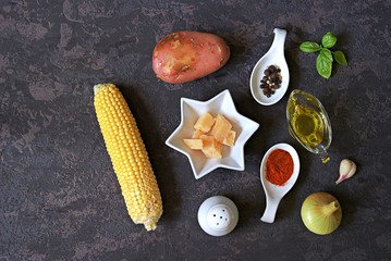 Ingredients for corn soup on a dark background: cob sweet corn, onions, potato, garlic, olive oil, paprika, salt, pepper, green basil, parmesan cheese. Italian food. Top view, copy space.