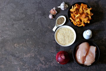 Ingredients for cooking pilaf with chicken and chanterelles: raw chicken fillet, chanterelles, basmati rice, red onion, cumin, garlic, salt. Top view. Cooking wild mushrooms. Mushroom season recipes.
