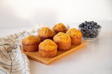 Freshly baked carrot muffins on a wooden board with tea towel and a bowl of blueberries on a white background