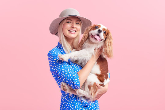 Cheerful pretty young woman in hat hugging her dog on pink isolated background. Lady owner in stylish blue dress and braces. The concept of a healthy smile and animal care