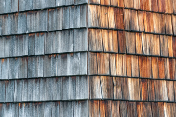 Weathered and faded from the sun wooden shingles that are the facade of an alpine house. Wooden texture in shades of gray and orange.