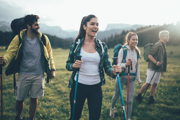 Adventure, travel, tourism, hike and people concept - group of smiling friends with backpacks and map outdoors Wall mural
