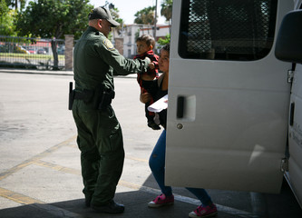 A U.S. Border Patrol agent assists a migrant woman and child in getting out of a transport van as they're released from federal detention with fellow asylum seekers at a bus depot in McAllen