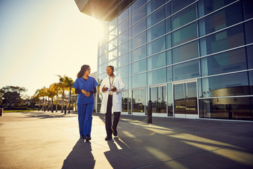 Doctor and nurse talking to each other outside hospital