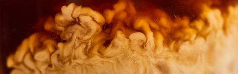 close up view of coffee mixing with milk in glass, panoramic shot