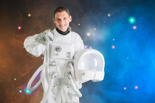astronaut holding helmet space suit and smiling