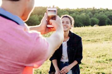 Man taking picture of woman with smartphone