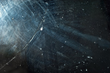 white dust and scratches on a black background. The texture of dirt on the glass.