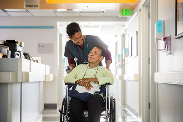 Nurse pushing senior woman in wheelchair in hospital
