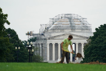 A man shovels dirt in front of the Washington Monument as workers do repairs on the Jefferson Memorial in the distance in Washington