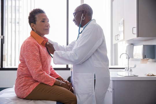 Side view of doctor examining patient with stethoscope in hospital