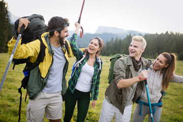 Adventure, travel, tourism, hike and people concept - group of smiling friends with backpacks and...