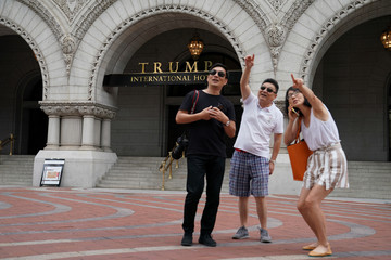 A group of people point to a person in a window of a building across the street after posing for photos in front of Trump International Hotel in Washington