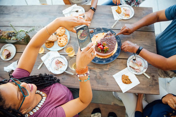 Overhead view of woman taking picture of cake with smartphone