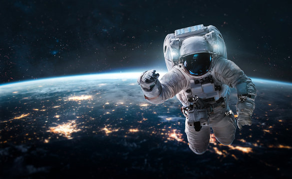 Astronaut in the outer space over the nightly planet Earth. City lights. Abstract wallpaper. Spaceman. Elements of this image furnished by NASA