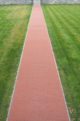 Straight red brick path in a lawn