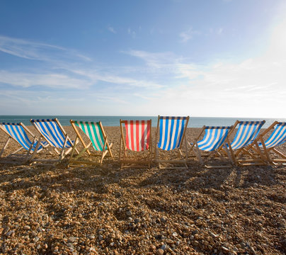 View of deckchairs on pebble beach against cloudy sky