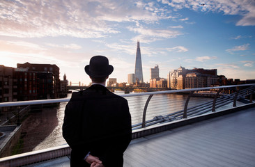 Rear view of man in bowler hat standing on Millennium Bridge