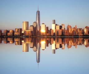 Skyline of Lower Manhattan reflected in calm Hudson River
