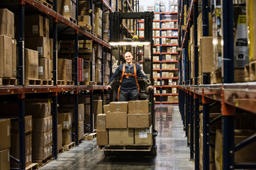 Portrait of man standing in stock picker loaded with cardboard boxes