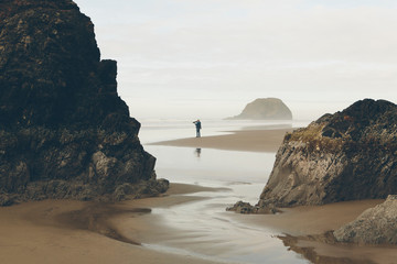 Man photographing on Arcadia Beach State park, Oregon, USA