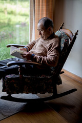 Senior man reading book while sitting on rocking chair at home