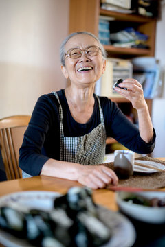 Smiling senior woman eating sushi while sitting at table