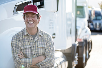 Portrait of truck driver standing near truck at truck stop