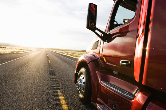 Commercial truck driving on road at sunset