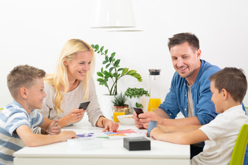 Happy young family playing card game at dining table at bright modern home. Spending quality leisure time with children and family concept. Cards are generic and debranded.